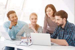 Gruppe Mitarbeiter schaut auf Laptop