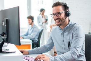 Service-Mitarbeiter im Gespäch mit Headset am Computer